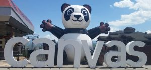"Large inflatable panda with ""canvas"" in white letters"