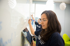 Woman using a tablet and whiteboard