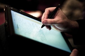 Person hand writing notes on tablet