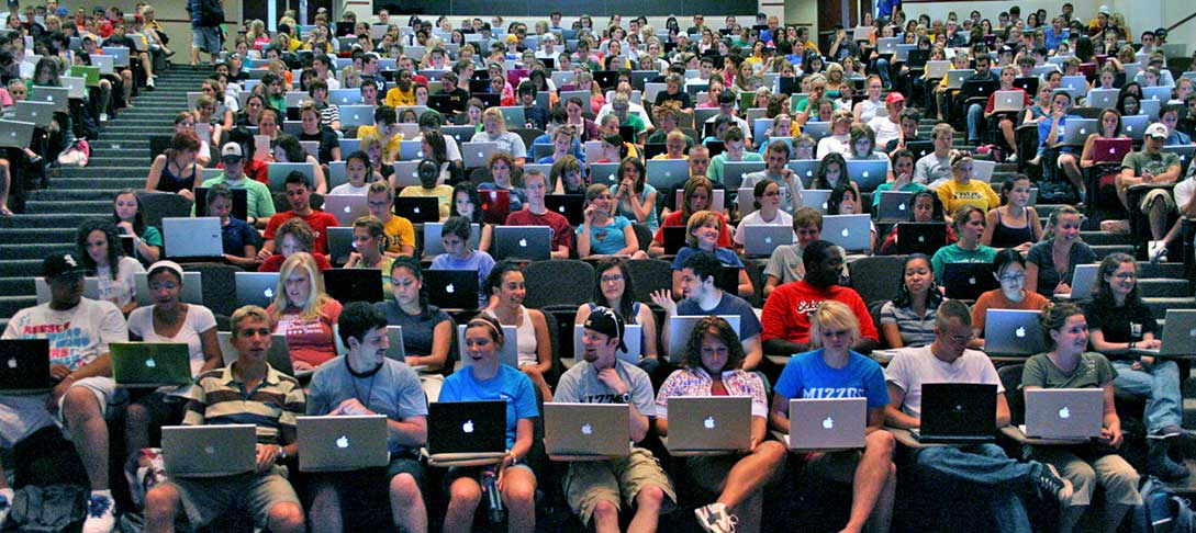 Students sitting with laptops in a lecture style classroom