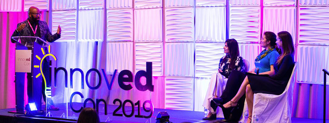 Image of host facilitating a panel discussion on stage
