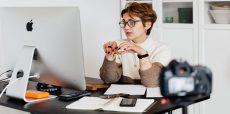 Woman at Mac computer filming herself at desk