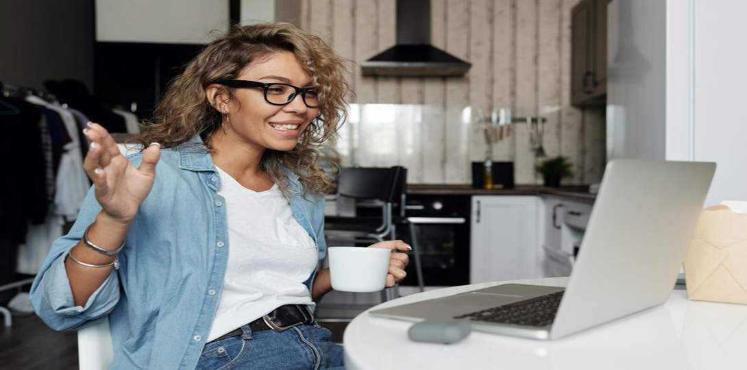 Woman with coffee cup waving greetings looking at laptop screen
