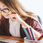 Woman biting yellow pencil in her mouth in front of a computer
