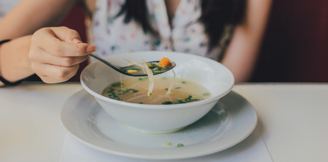 Woman with long hair holding a spoon over a white bowl of chicken noodle soup